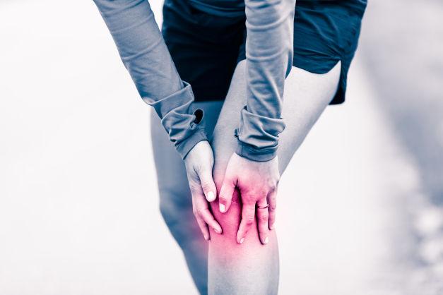 Γυναίκα που κρατάει γόνατο που πονάει.